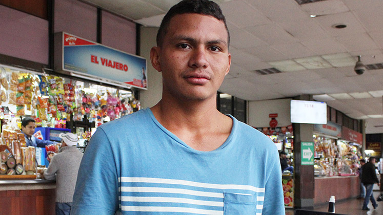 A Venezuelan migrant at a Colombian market looks into the camera