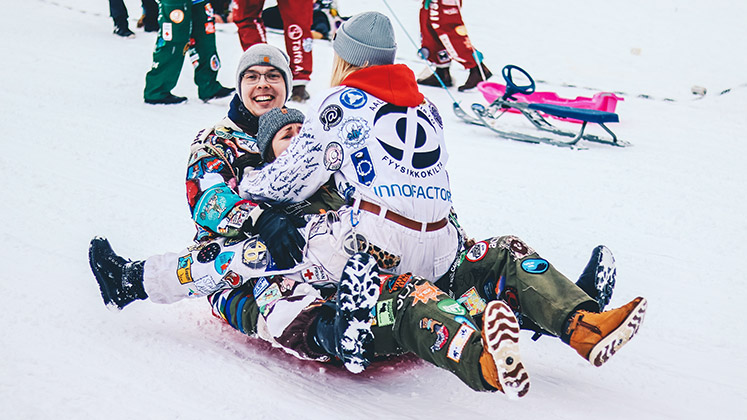 Three Finnish people going down a hill on one sledge