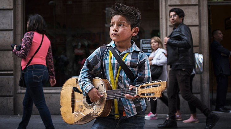 A boy with a broken guitar busks in Mexico City as shoppers wander by