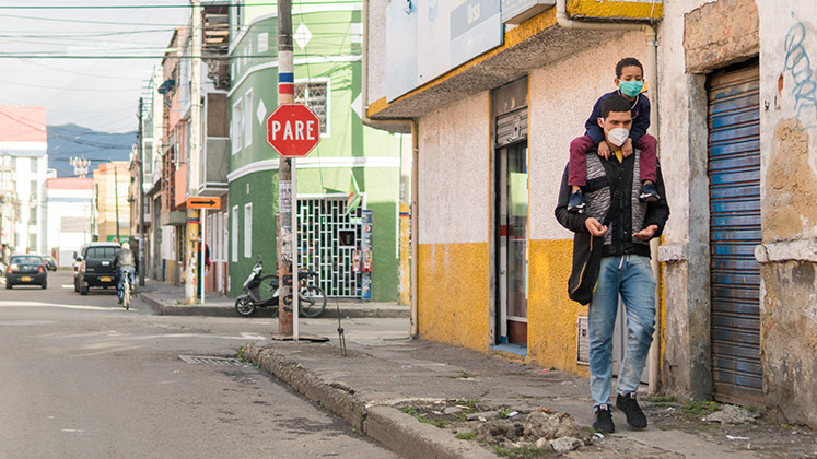 A father carries his son on his shoulders through the streets of Bogota, both wearing masks for COVID-19