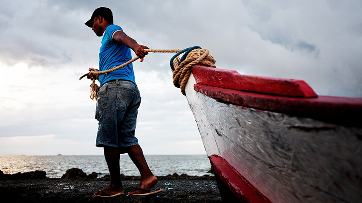 A fisherman pulls a red and white boat into the water near Belem