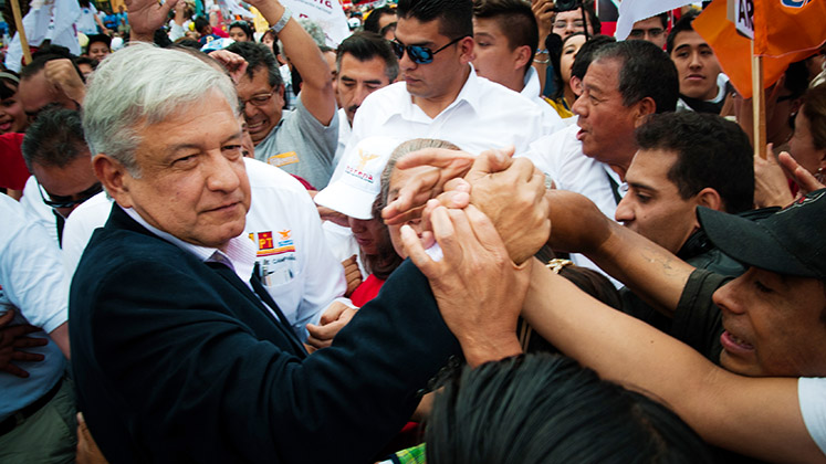 AMLO shakes hands with supporters at a rally