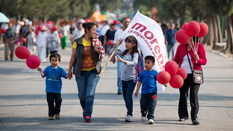 A family walks through Mexico City with red balloons and a flag of the Morena political party