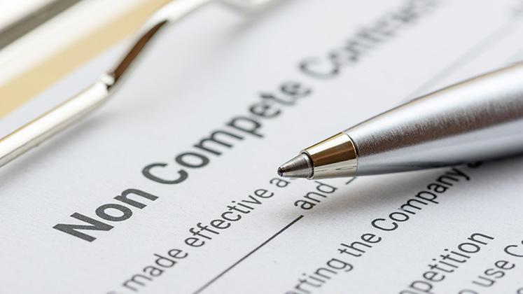 A pen hovers above a contract with non-compete written at its head