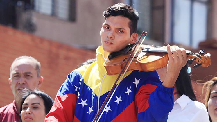 A violinist in a Venezuela tracksuit plays during a protest