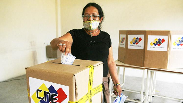 A Venezuelan woman votes in a ballot box bearing the logo of the National Electoral Council