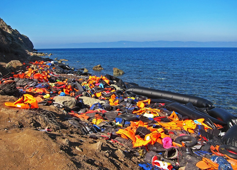 multicoloured life jackets strewn on a beach