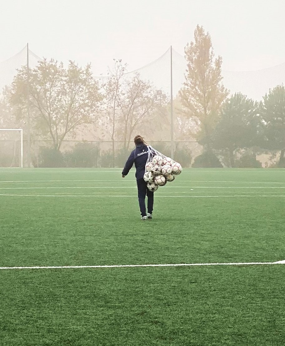 person carrying bag of footballs on football field