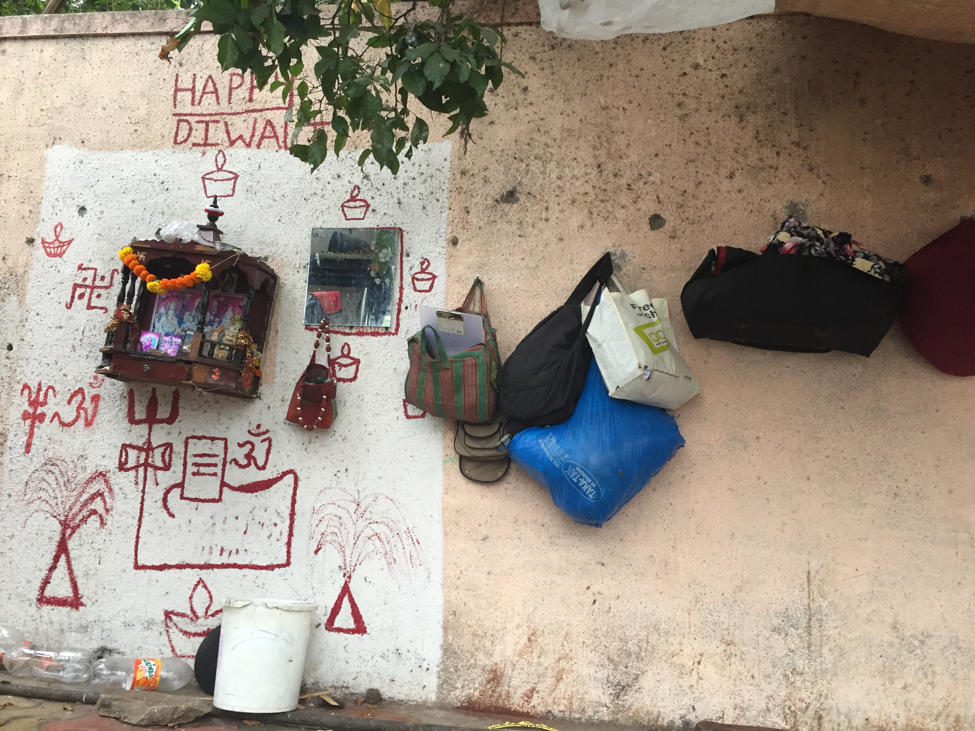 A footpath with a makeshift shrine and bags hung on the wall