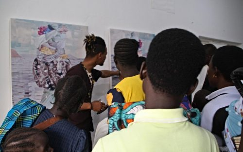 Artist explaining his work to South Sudanese women who participated in the artwork's creation