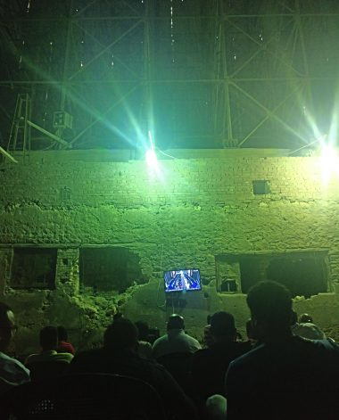 residents watching a football match on a demolished building site