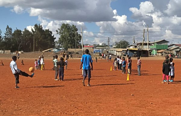 Mukuru youth in Kenya playing football on a pitch