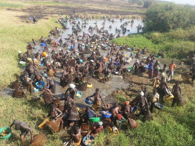 Acholi women and children using traditional fishing baskets along River Agago