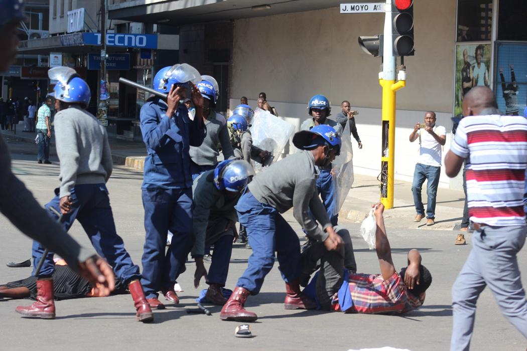 Police beat up a protester on the street during an opposition demonstration