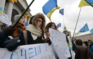 Image of protesters in winter coats holding banners and EU and Ukranian flags
