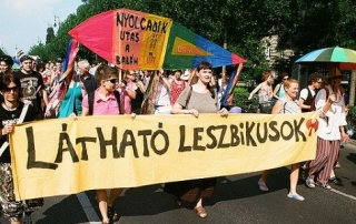 People carrying a large banner and a sign in rainbow colours