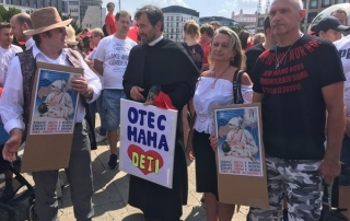 A priest and other protesters holding signs