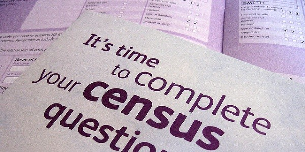 Two overlaid census forms, front page of census booklet in the foregrround reads: It's time to complete your census questionnaire