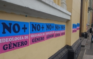 Outside wall of a building with a row of poster stickers in blue and pink that read No + ideología de género in all capital letters