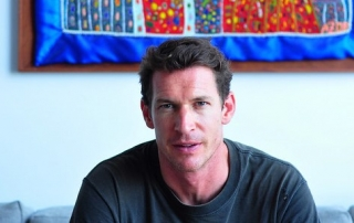 Image of a man, Tim Hetherington, sitting on a couch looking straight at the viewer, with a colourful tapestry above his head