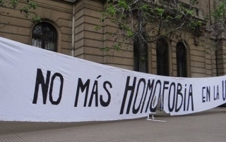 "White banner outside a building with message ""No más homofobia en la UC"""