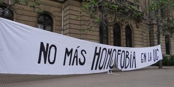 "White banner outside a building with message ""No más homofobia en la UC"""