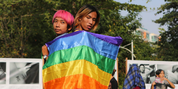 Picture of two young people holding rainbow flag