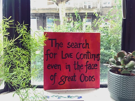 handwritten sign on a windowsill with potted plants to either side. The text reads The search for LOVE continues even in the case of great ODDS.