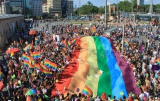 Crowd holding rainbow pride flags
