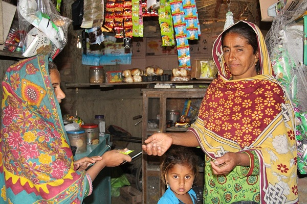 Two women completing a transaction in a shop