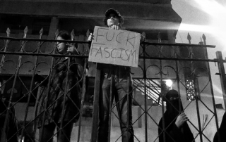"Photo of protester holding sign ""fuck fascism"""