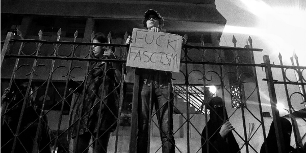"""Photo of protester holding sign """"fuck fascism"""""""