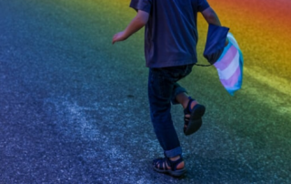 A child runs underneath the rainbow flag in Portland, Maine during the Pride Parade
