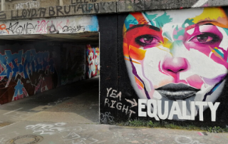 "Street art image of woman's face with the word ""Equality"""