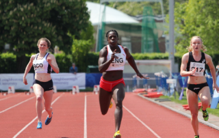 Three women athletes sprinting, the middle athlete - Black woman - appears to be winning