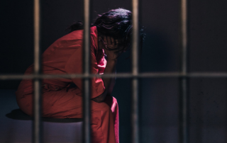 Woman in prison cell, seen through bars with her head in her hands