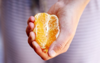 Orange half, cupped in a woman's hand (suggestive in shape)