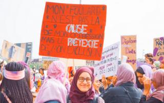 """Hijabi holding protest sign reading """"mon foulard n'est pas la cause de mon oppression mais le pretexte de mon exclusion"""""""