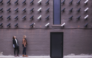 Two women on a street looking up at multiple rows of security cameras, all of which are pointed at them