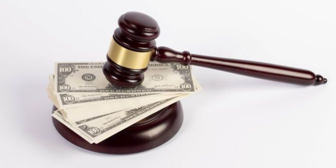 Photograph of a gavel on top of a pile of US dollars