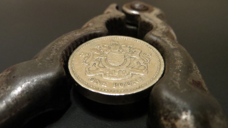 Pound coin being squeezed between a nutcracker
