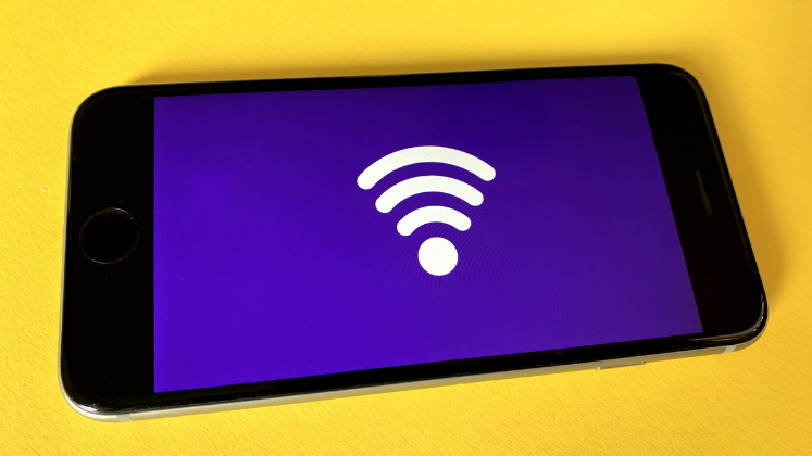 Mobile phone on yellow background showing the WiFi icon