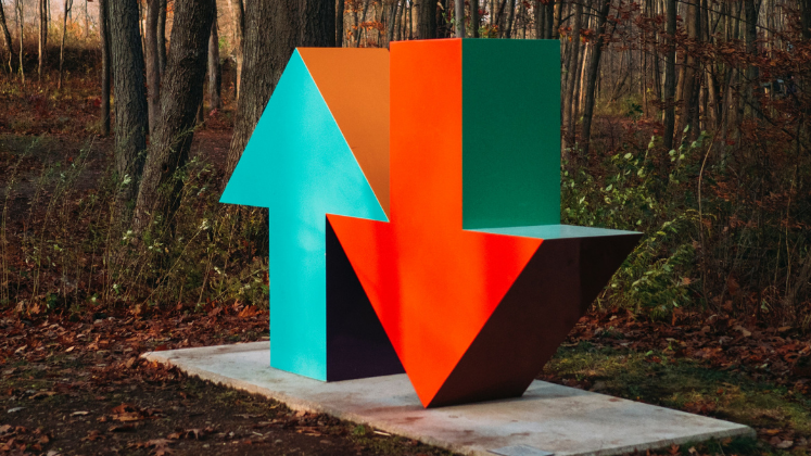 Sculpture of up and down arrows next to one another, set in woodland