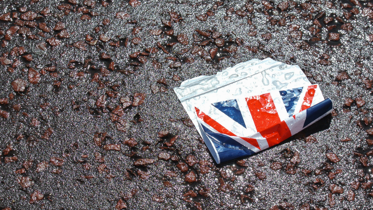 Sticker of Union Jack lying on wet pavement