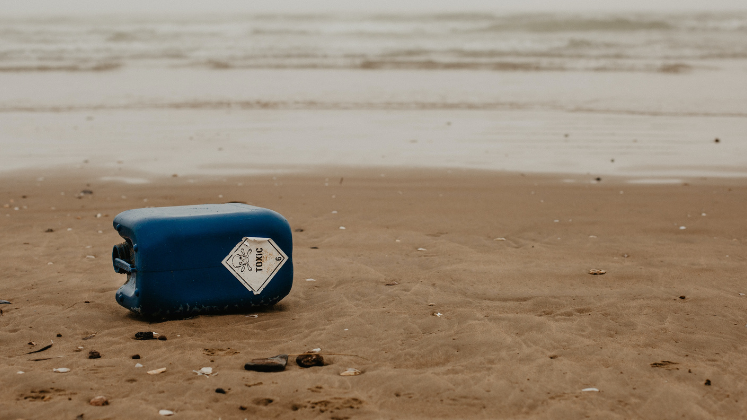Blue can labelled 'toxic' lying on beach