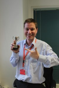 Image of Nicos at LSE, holding a trophy