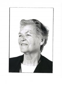 Black and white image of Ailsa Land with short hair and a dark jacket, against a white background