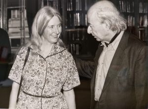 Lucien Foldes on the right in conversation with a female colleague. The image is black and white, and the two are in a library.