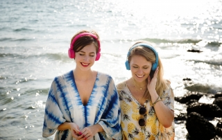 women listening to music on beach