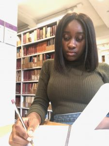 Student Ebun writing in the library